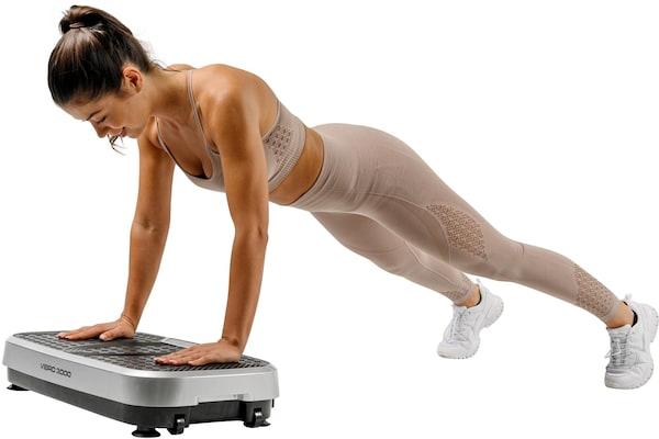 Frau trainiert Oberkörper auf Vibrationsplatte
