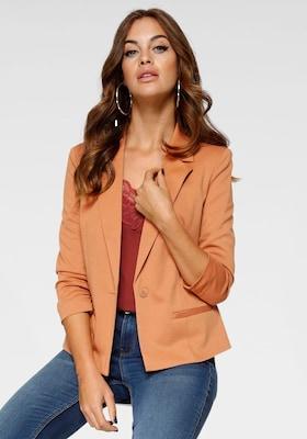 Model mit Damen-Jeans, rotes Spitzenshirt und orangen Blazer von VERO MODA