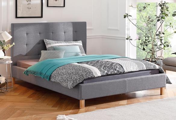 graues Polsterbett mit Holzfüßen